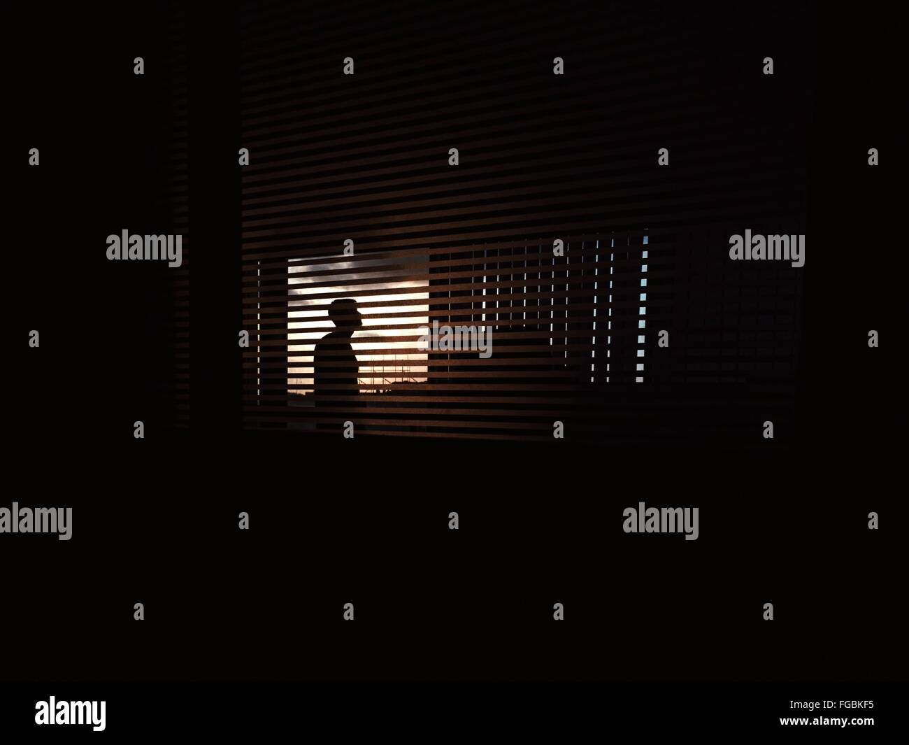 Silhouette Man Seen Through Blinds Window - Stock Image