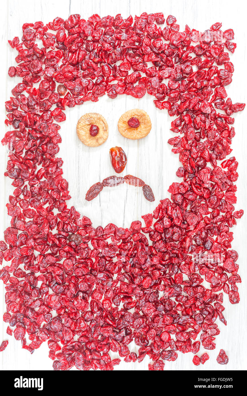 Sad face made of dried fruits on white wooden background. - Stock Image