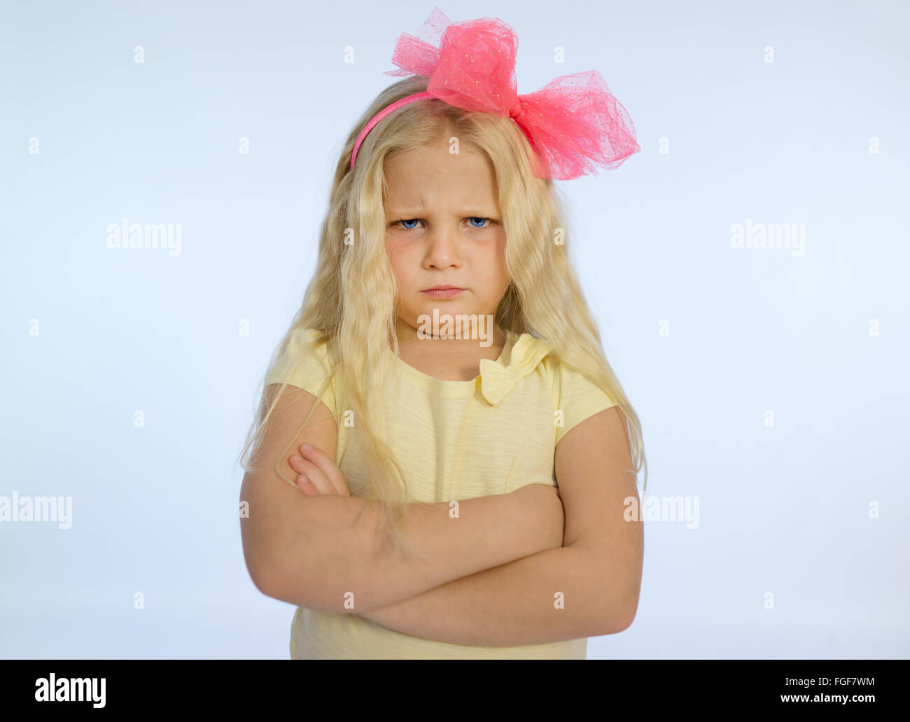 Young girl with long blonde hair and folded arms, frowning with a sad and grumpy expression - Stock Image
