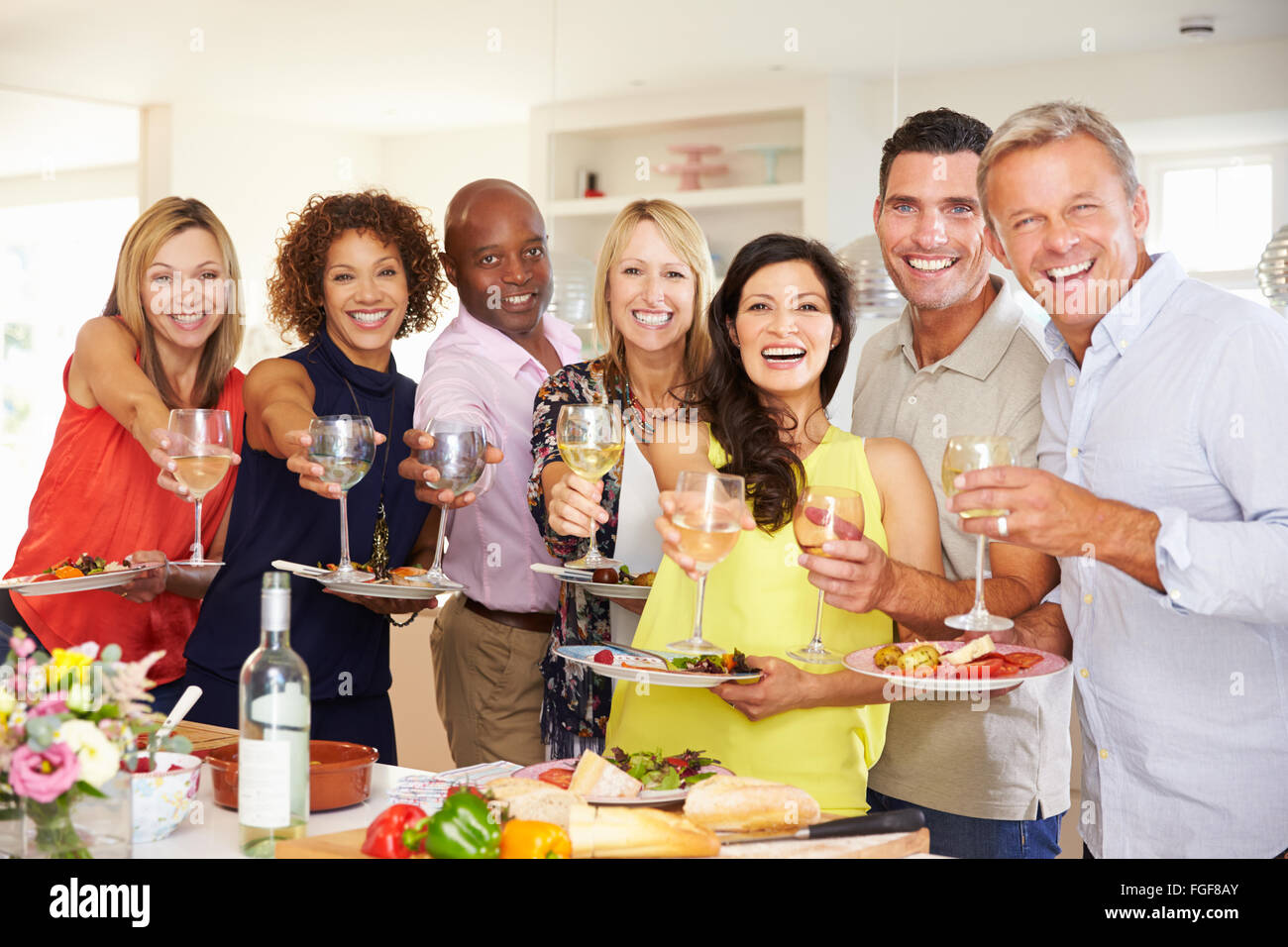 portrait of mature friends enjoying dinner party at home stock photo