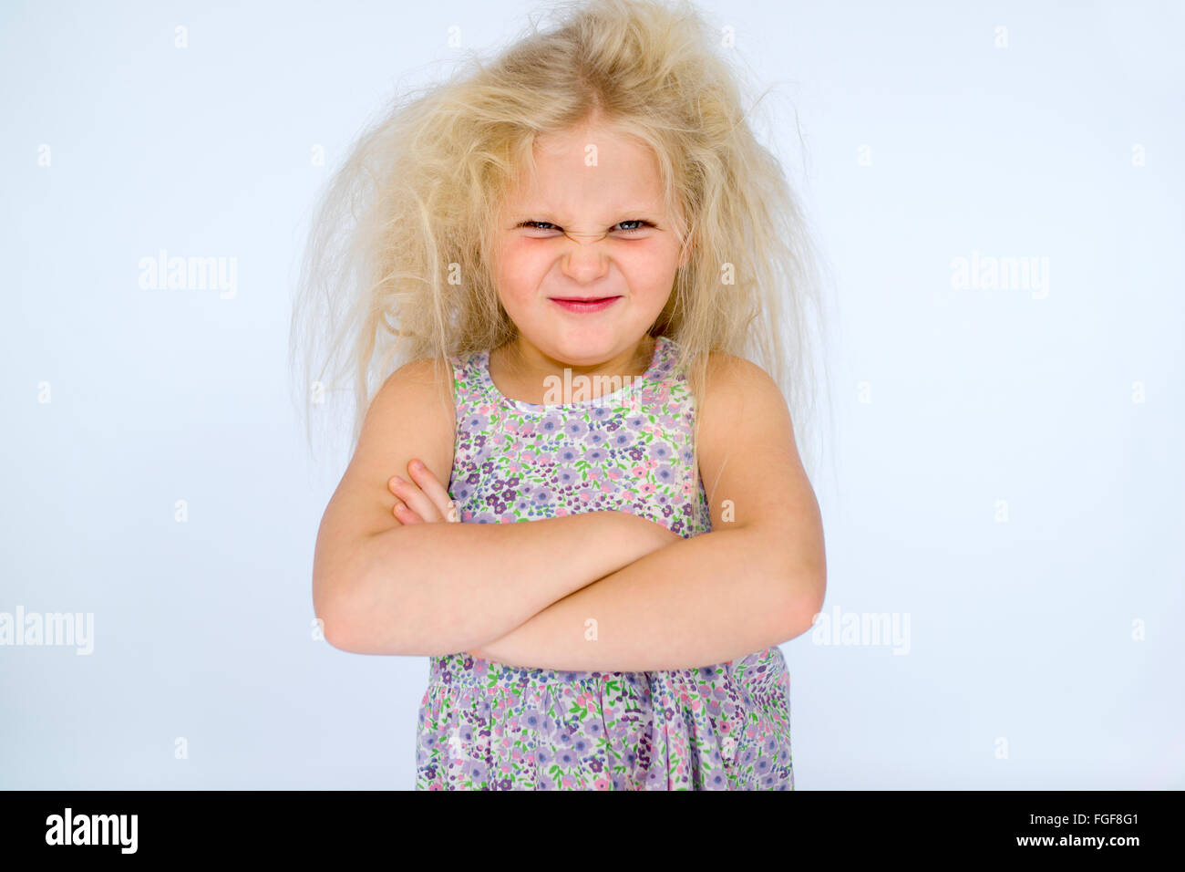 Young girl with messy blonde hair frowning with folded arms and a cheeky grin - Stock Image