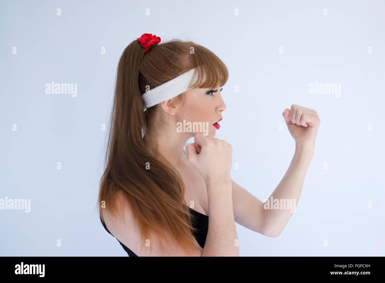 Woman with long brown hair wearing a head sweatband with her fists clenched preparing to engage in boxing - Stock Image