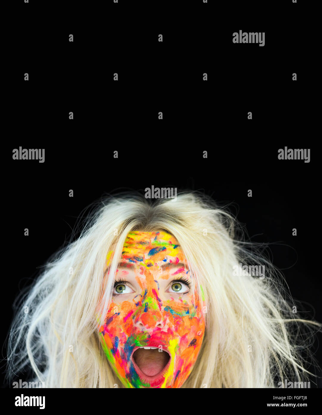Woman with messy blonde hair and face covered in multi coloured paint with a surprised expression - Stock Image