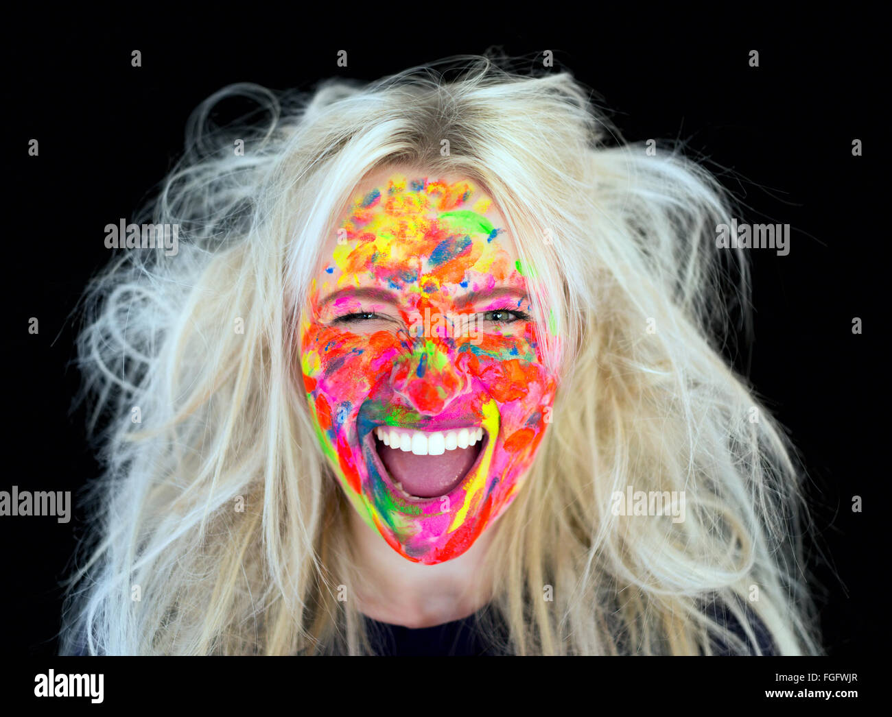 Woman with messy blonde hair with face covered in multi coloured paint laughing - Stock Image