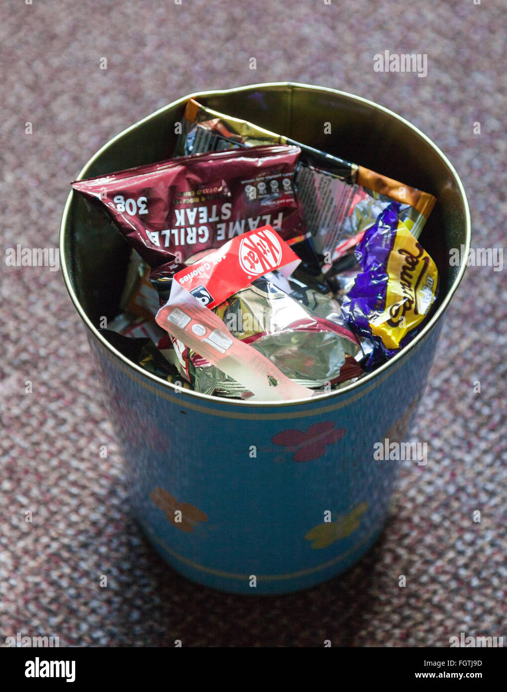 crisp-and-chocolate-bar-wrappers-in-a-waste-paper-bin-FGTJ9D.jpg