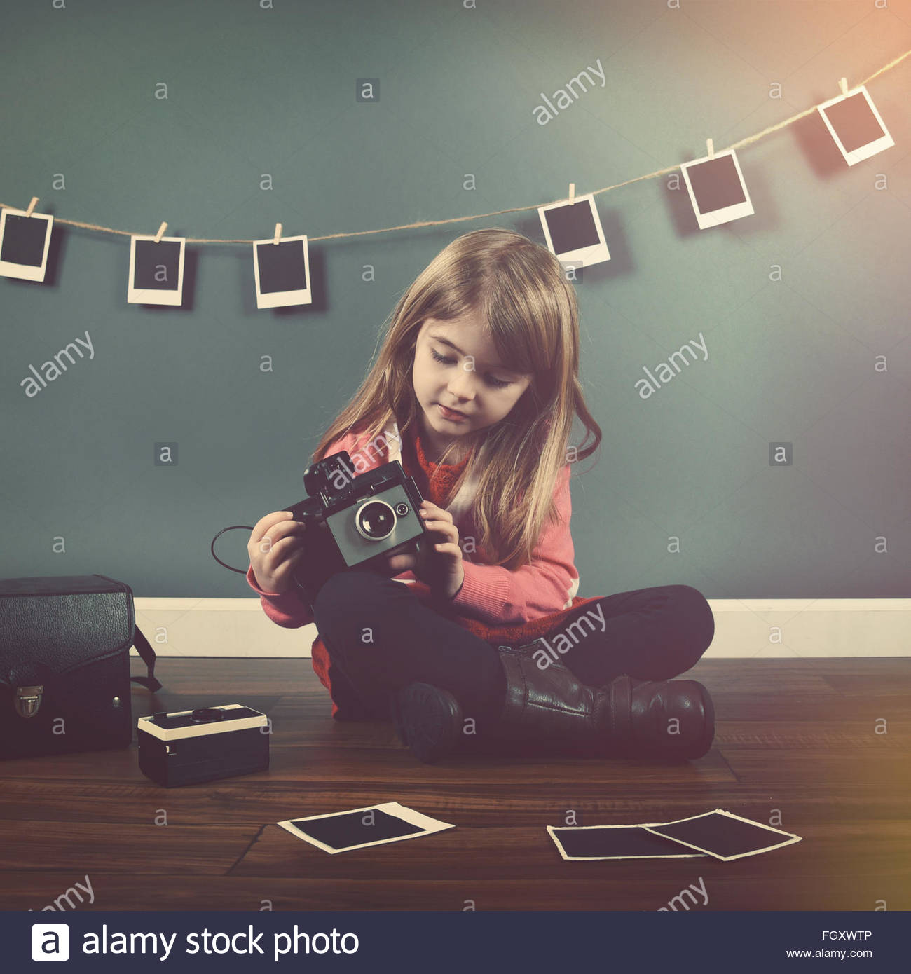 A photo of a vintage child taking a picture with an old camera and hanging pictures in the background for creativity. - Stock Image