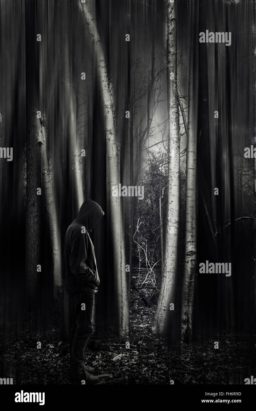Man with hooded jacket in forest, black and white - Stock Image