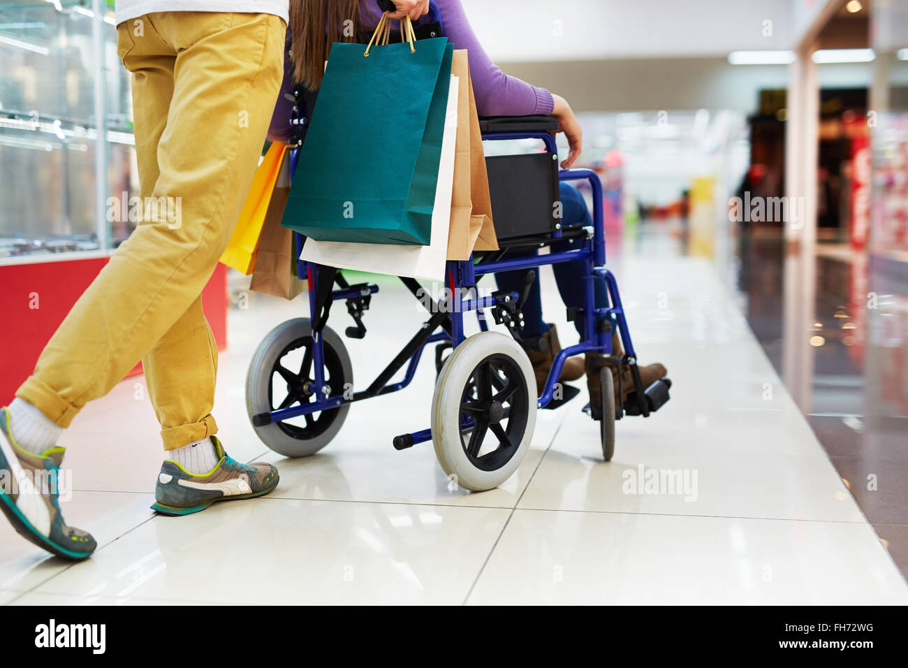 Caring guy helping his girlfriend on wheelchair with shopping - Stock Image