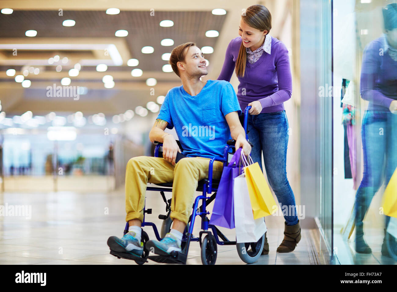 Caring girl talking to her boyfriend in wheelchair during sale - Stock Image