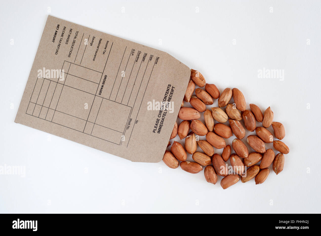 traditional pay packet full of peanuts monkey nuts cut on on a white background Stock Photo