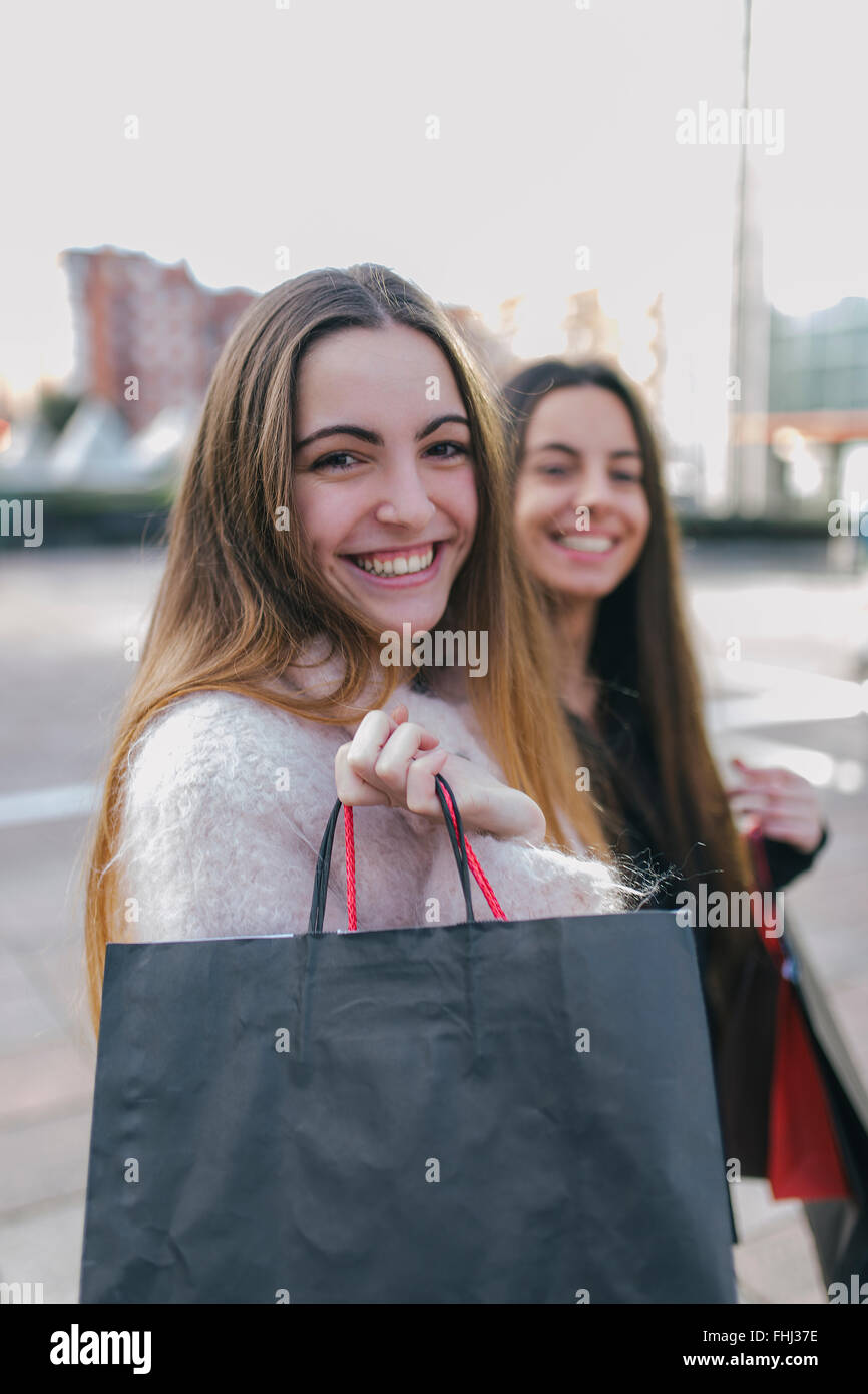 Portrait of happy young woman with shopping bags - Stock Image