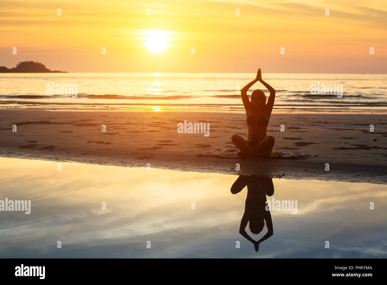 Silhouette of woman sitting on the beach during a beautiful sunset, with reflection in the water. - Stock Image