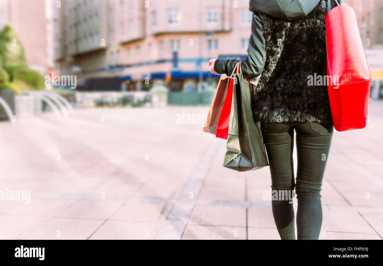 Back view of young woman carrying shopping bags - Stock Image