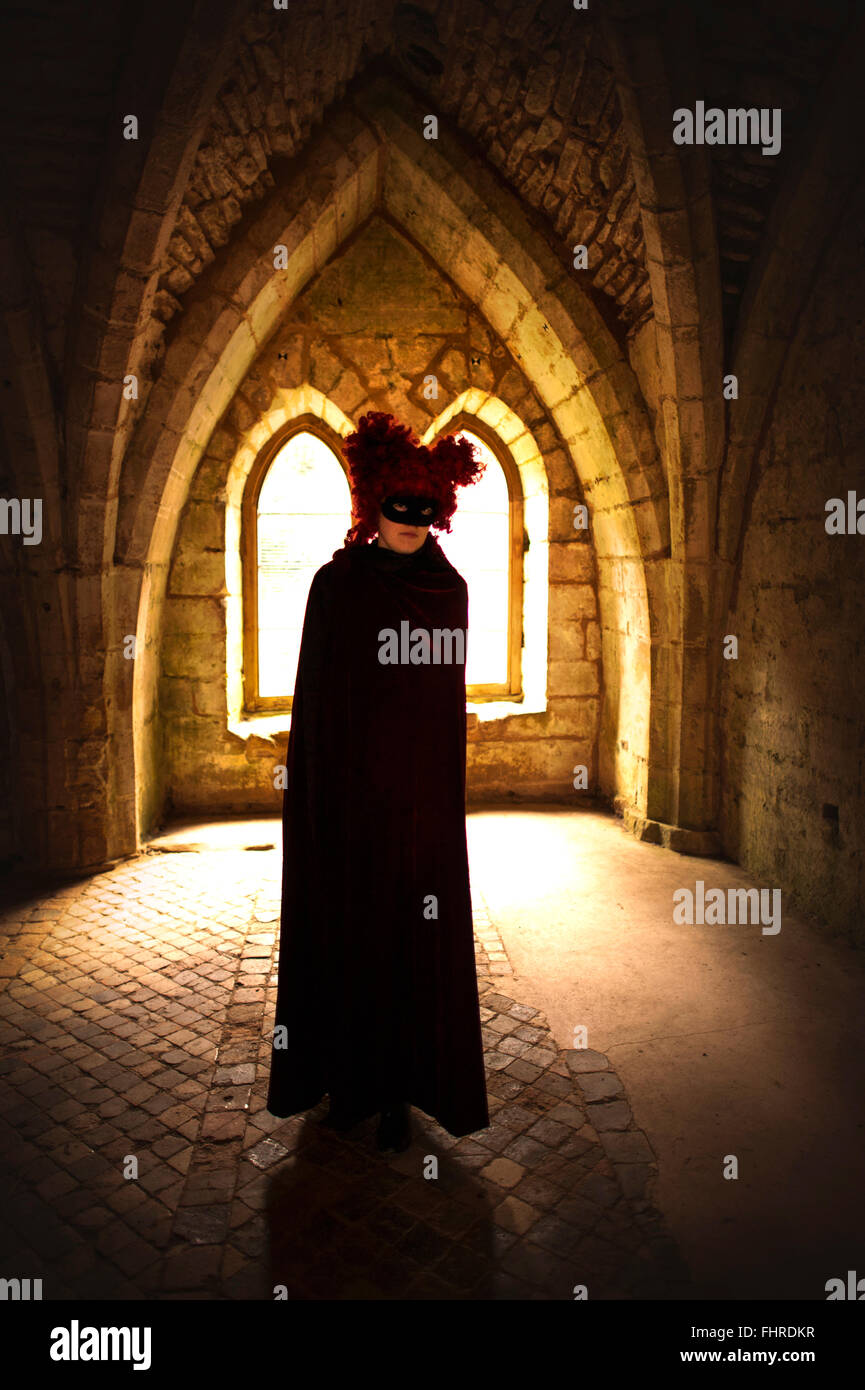 female figure wearing red wig  standing in castle - Stock Image