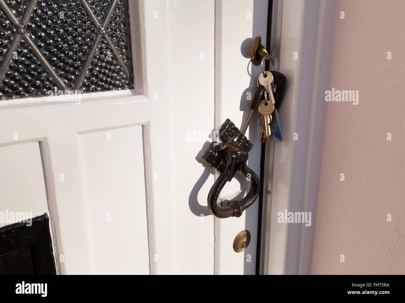 A house door with forgotten keys left in the lock, UK Stock Photo
