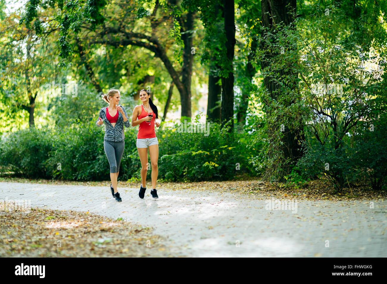 Sportive women jogging in park and listening to music through earphones - Stock Image