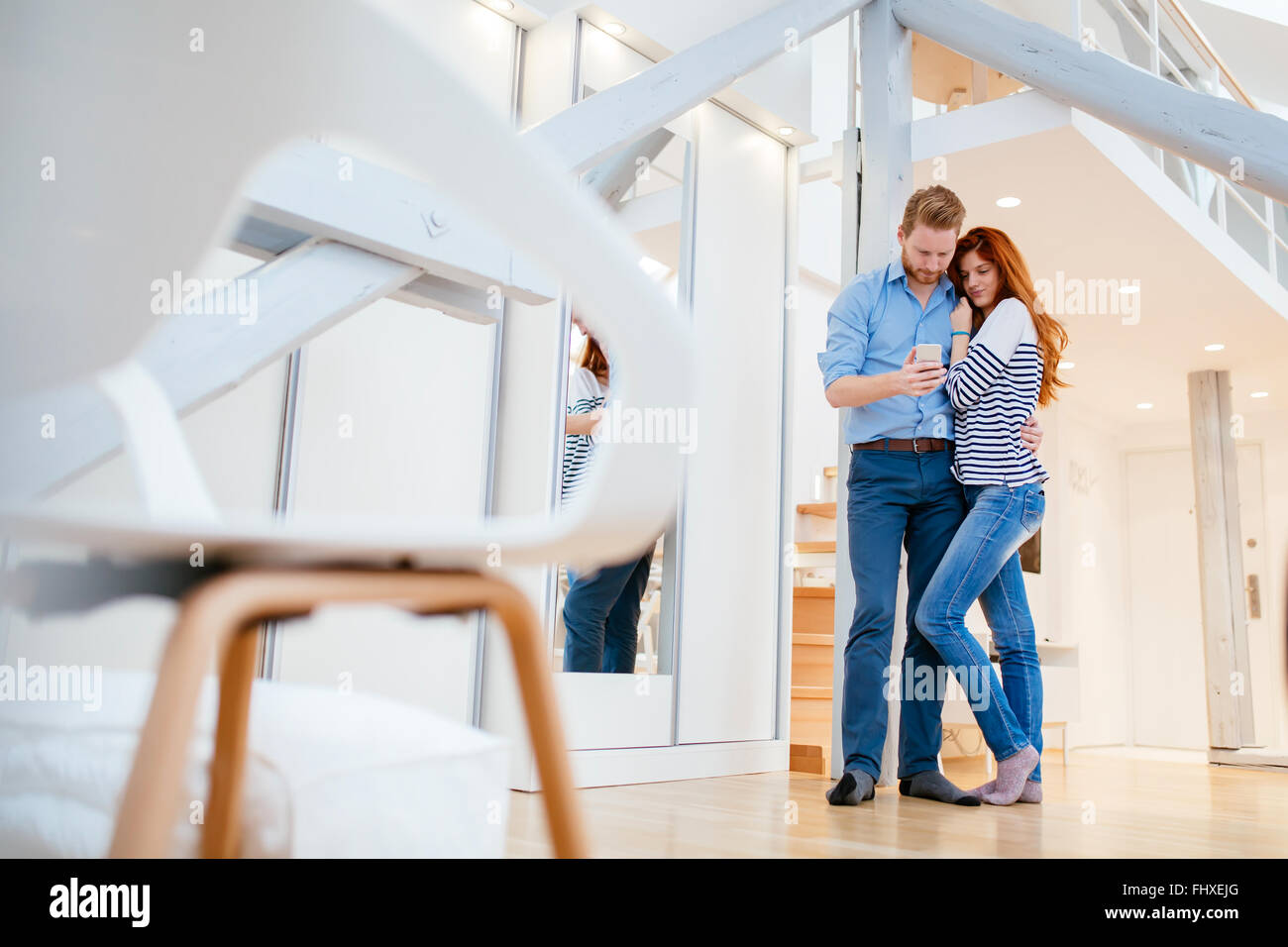 Couple enjoying their modern new well lit apartment - Stock Image