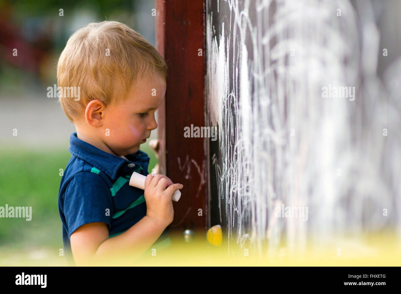 Creative cute toddler drawing with chalk outdoors on a drawing board - Stock Image