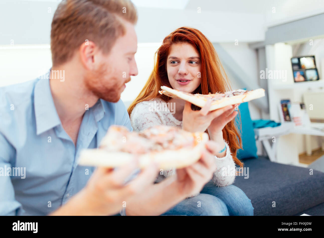 Couple sharing pizza and eating together happily - Stock Image