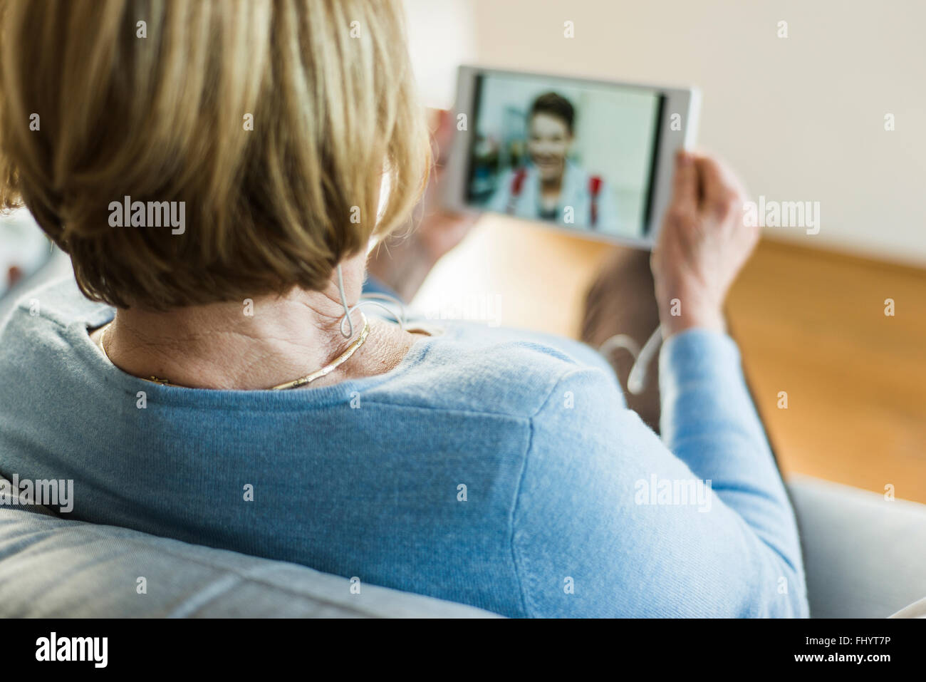 Senior woman looking at picture of young man on digital tablet Stock Photo