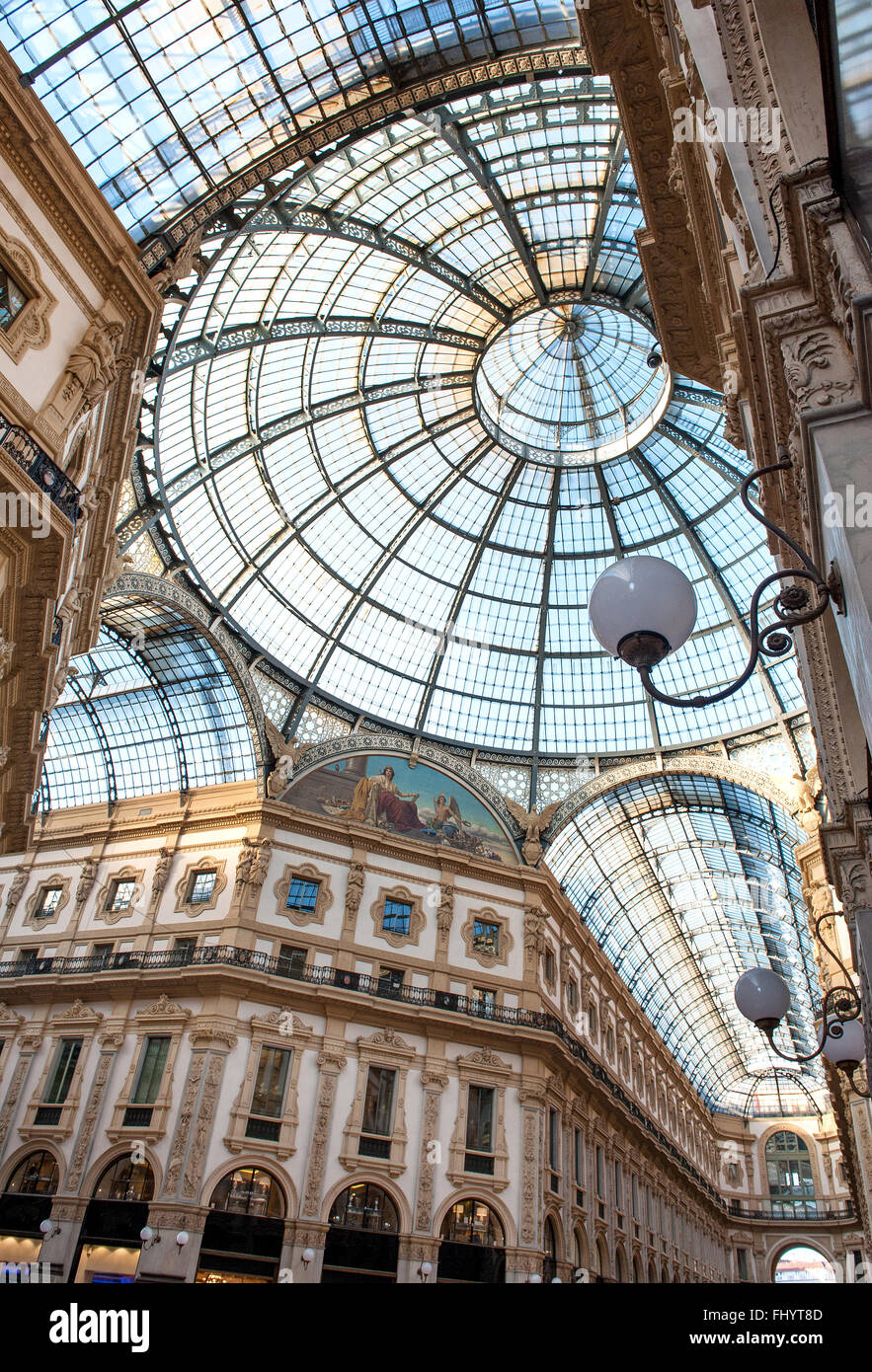 Low angle view of corridors and circular domed ceiling and windows inside the Vittorio Emanuele Milan shopping mall - Stock Image