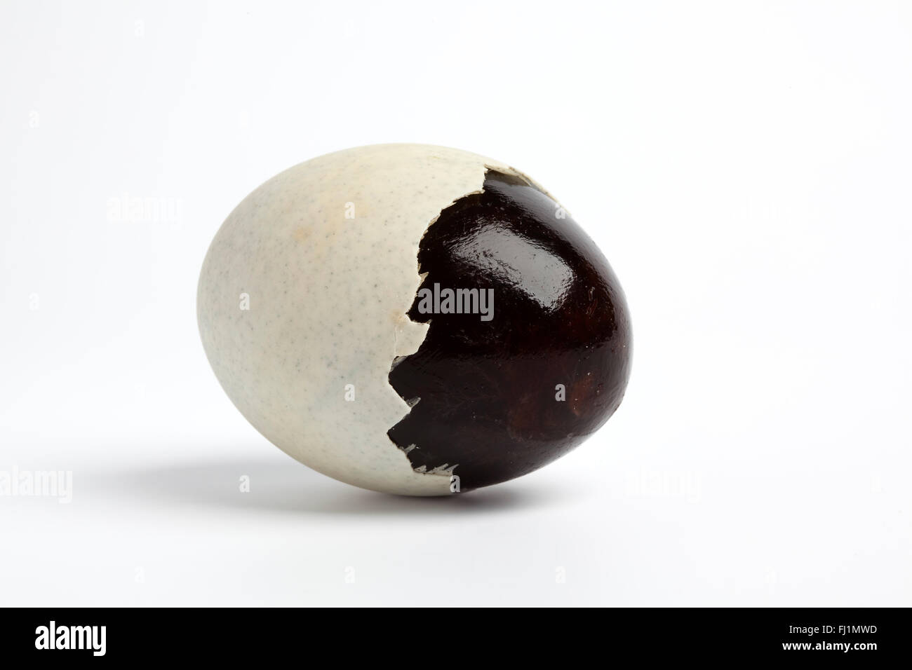 Partial peeled Thousand years duck egg on white background - Stock Image