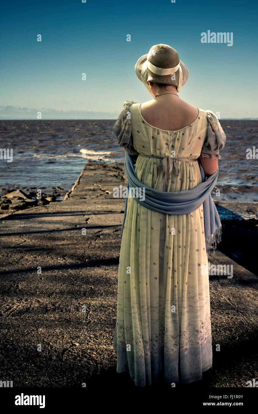 Regency dressed woman looking out to sea - Stock Image