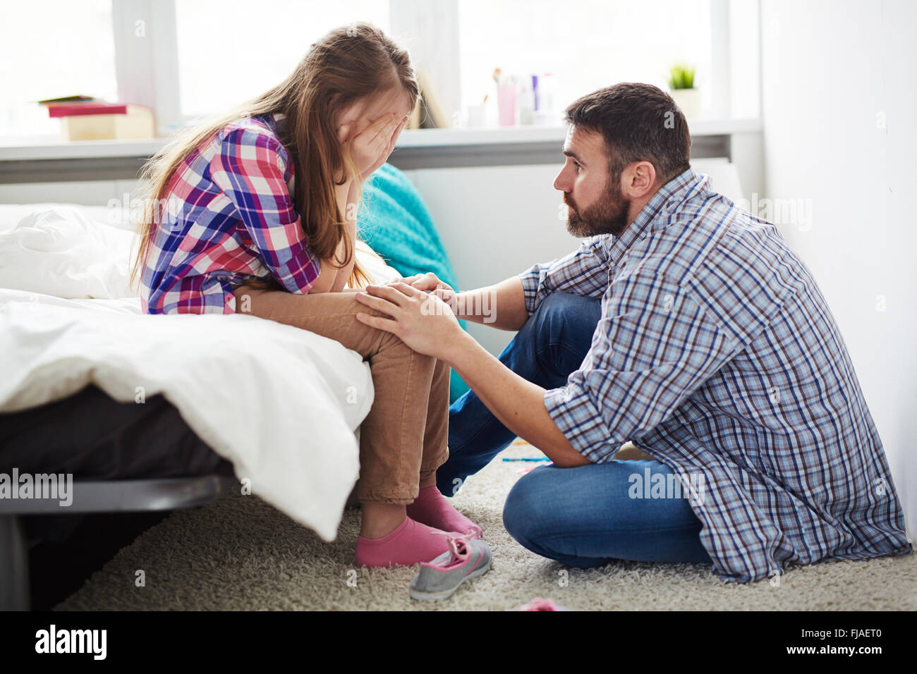 Teenage girl crying while her father reassuring her - Stock Image