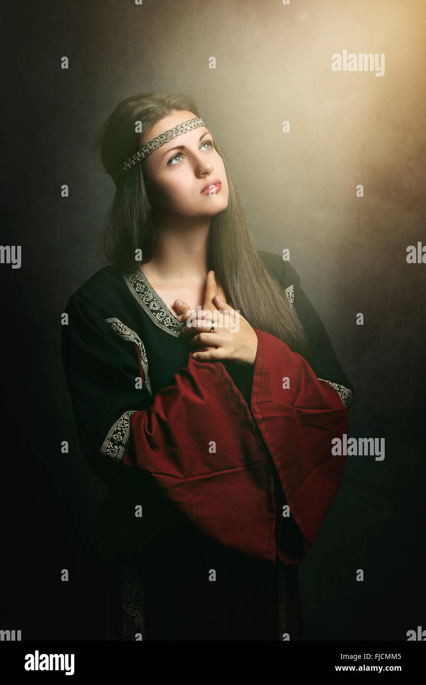 Beautiful medieval woman praying in soft holy light . Historical and religion - Stock Image