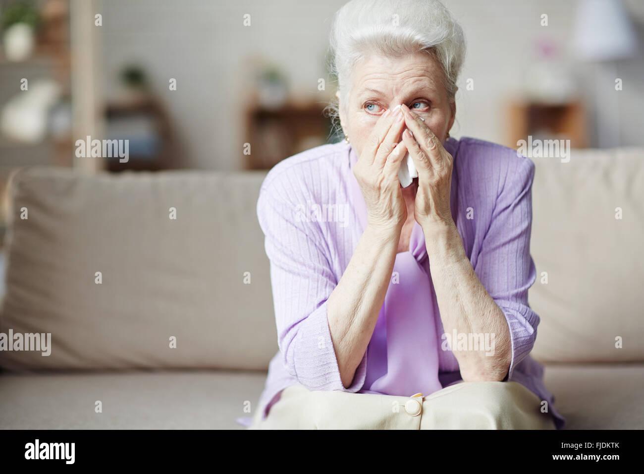 Sad senior woman sitting on sofa and crying - Stock Image