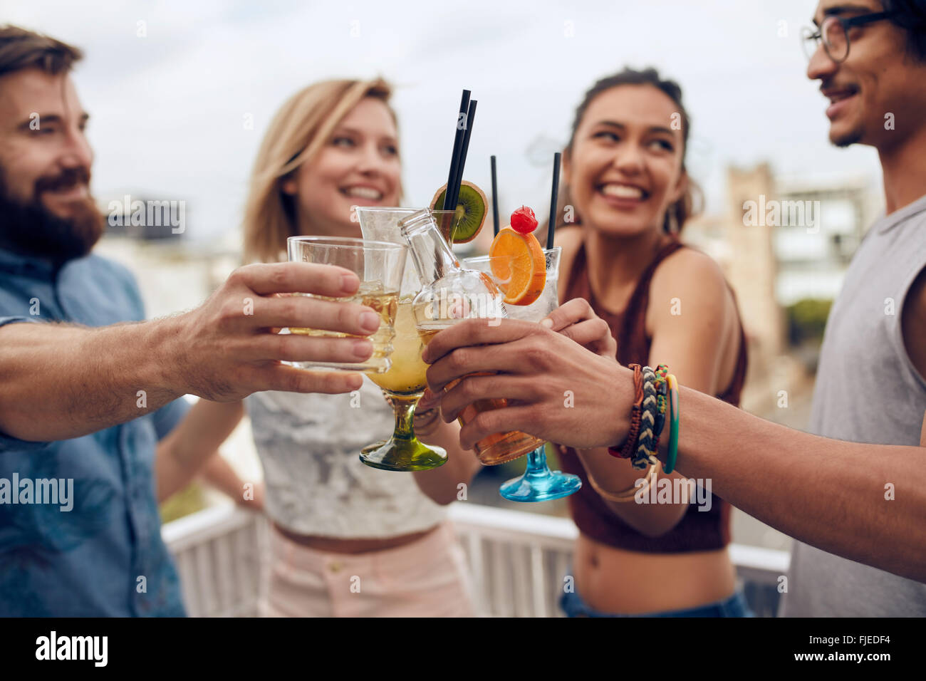 Friends having fun and drinking cocktails outdoor on a rooftop get together. Group of friends hanging out and toasting - Stock Image