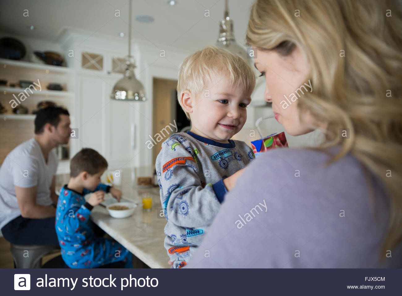 Son sharing juice box with mother in kitchen - Stock Image