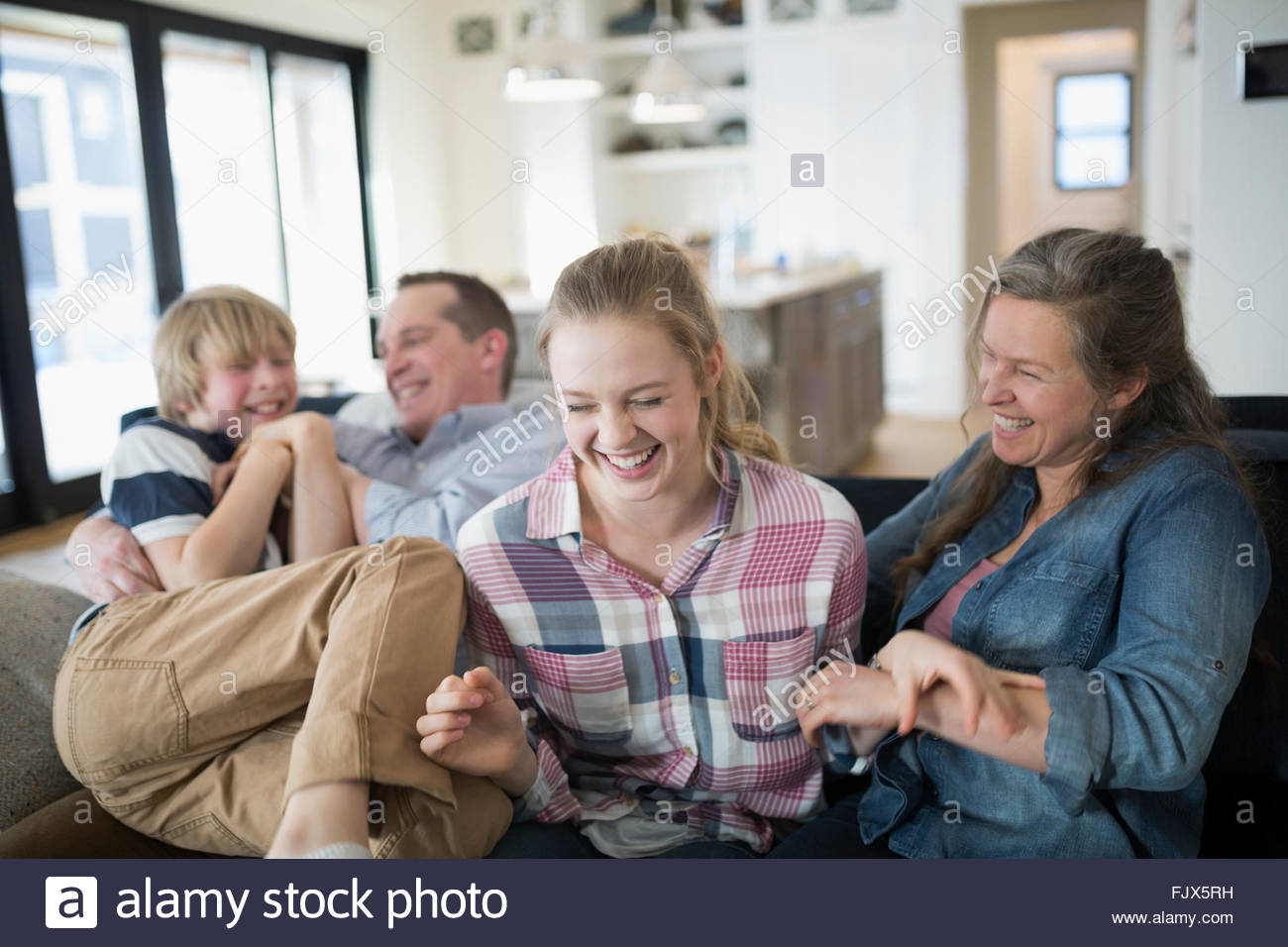 Laughing family on living room sofa - Stock Image