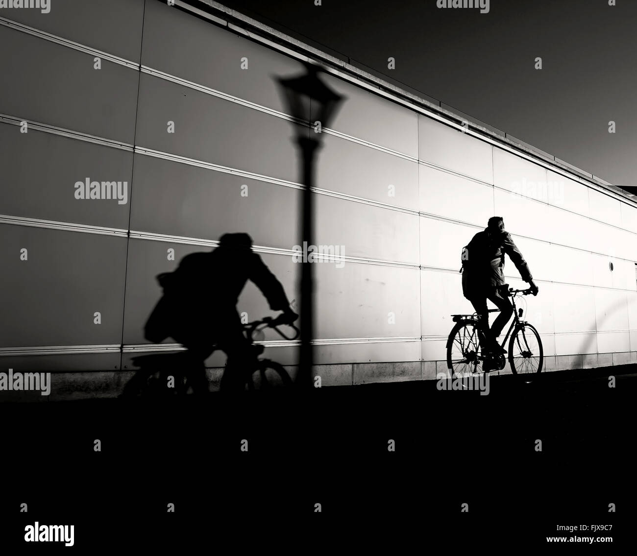 Man Riding Bicycle On Road By Wall Stock Photo