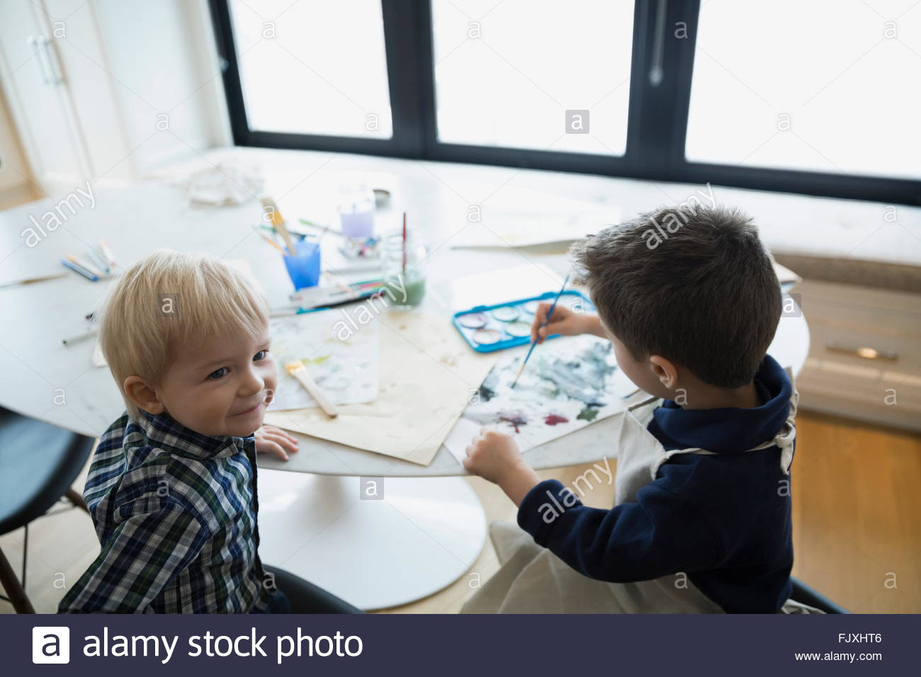 Brothers watercolor painting at table - Stock Image