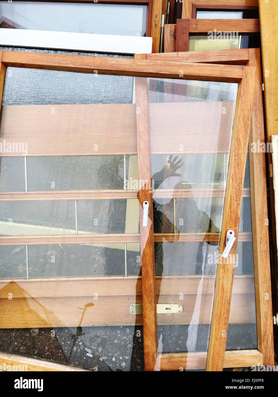 Reflection Of Man On Glass Door At Workshop - Stock Image