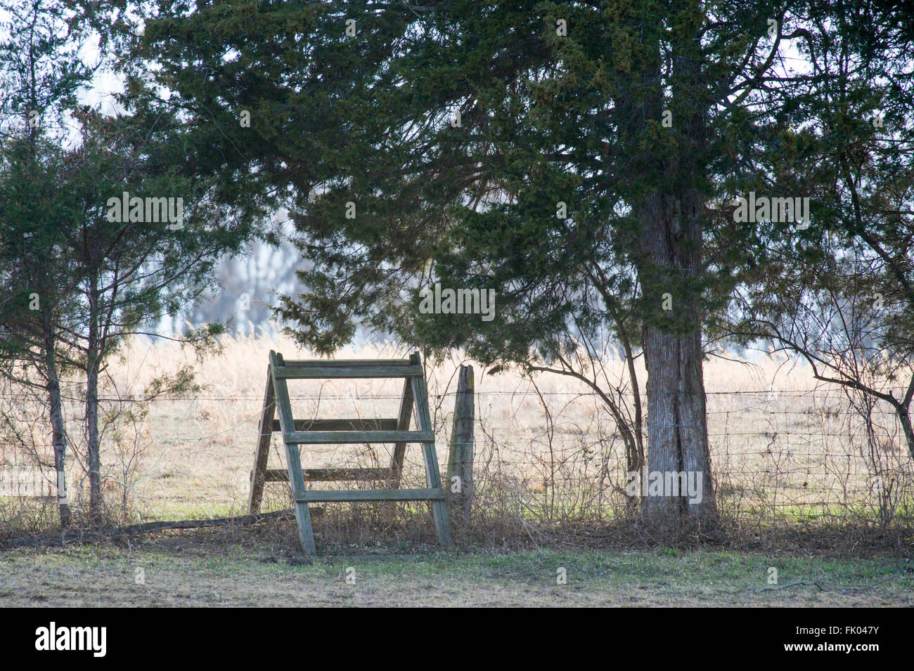 A rustic wooden stile crossing a wire fence between to pastures in ...