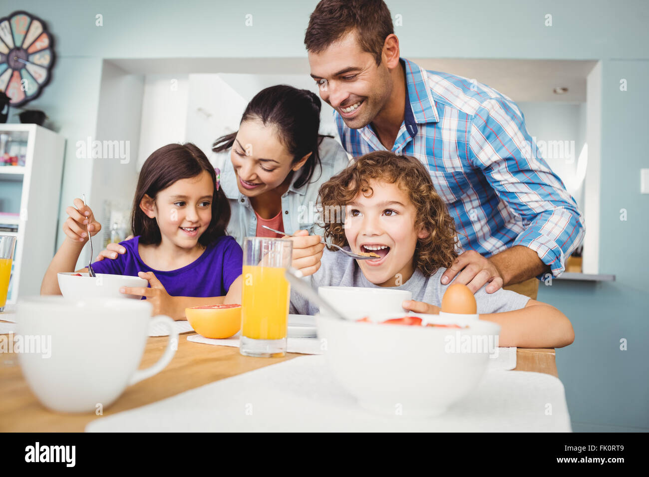 Cheerful man and woman with children during breakfast - Stock Image