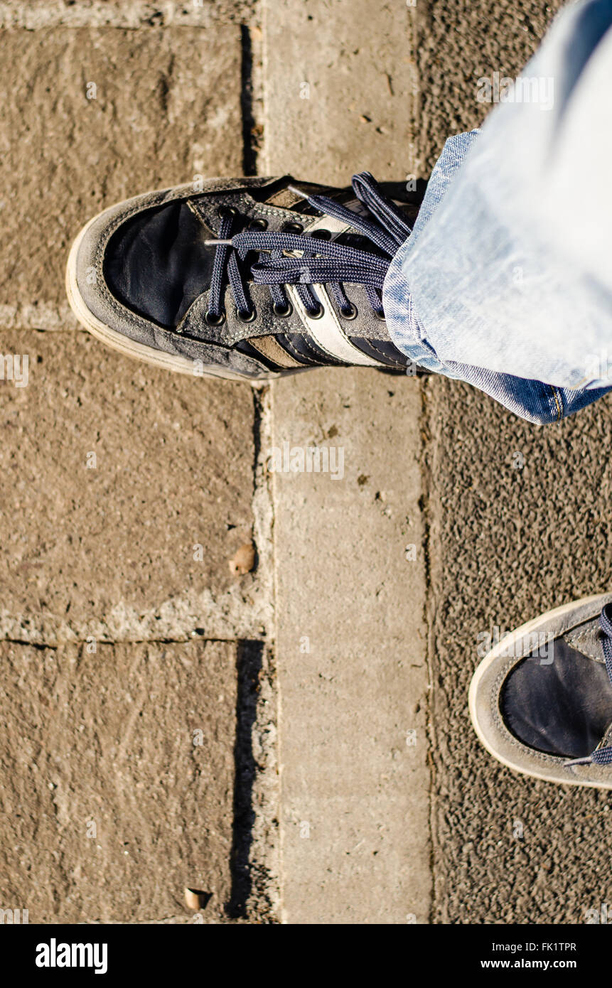 I walked the line, a step forward help to cross the line and overcome a block. passage from concrete to stone paved - Stock Image