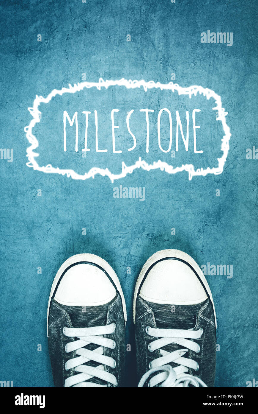 Young man standing on the street, milestone marking on road, concept of breakthrough achievement - Stock Image