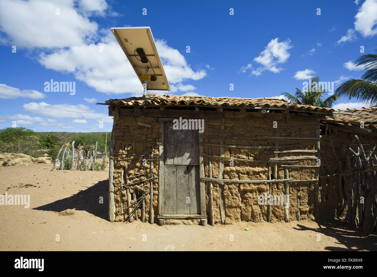 House of wattle and daub with funding solar panel for generating electricity for - Stock Image