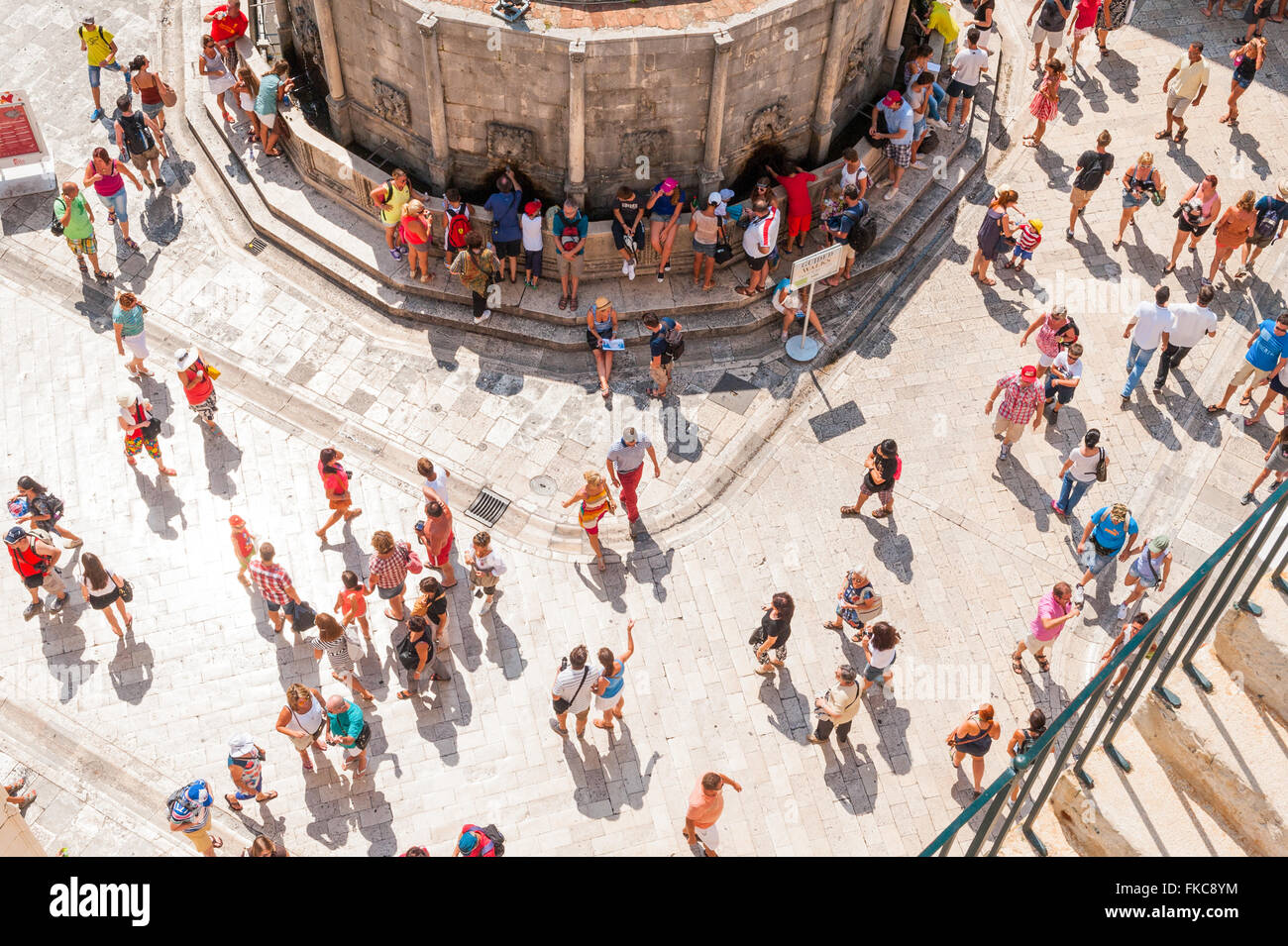 Crowds of holiday makers enjoy the sun and sightseeing around the old historical city of Dubrovnik in Croatia. Stock Photo