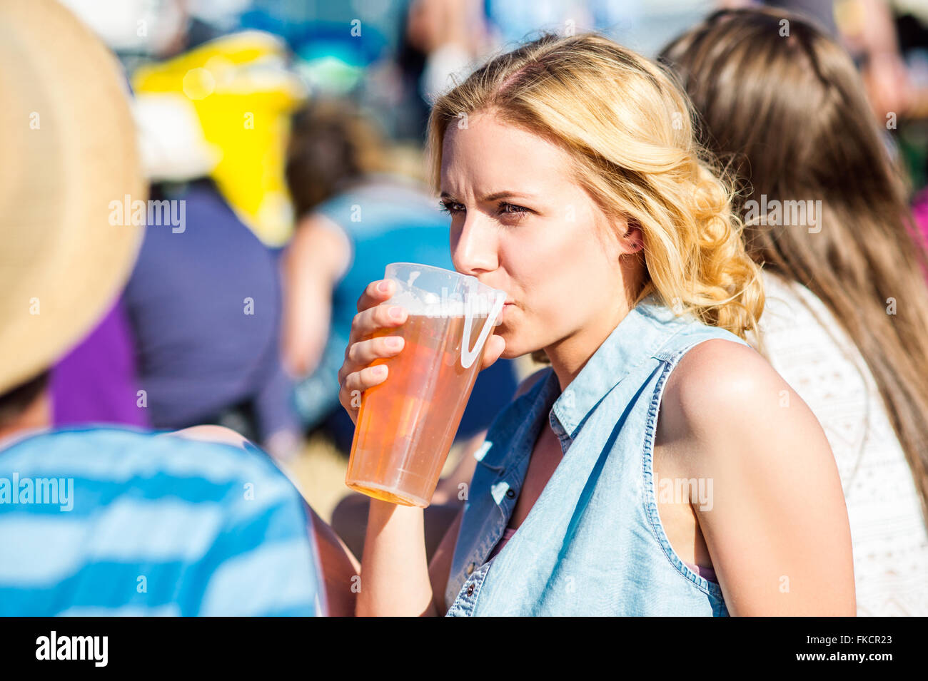 Young blond woman with beer at summer music festival Stock Photo