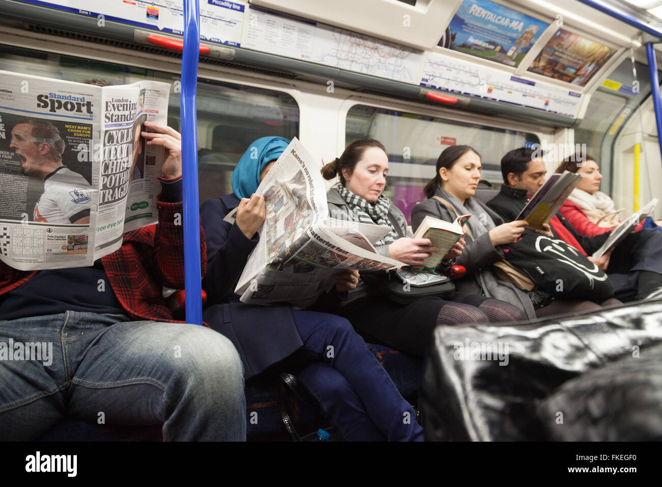 Passengers reading books and newspapers in a London underground train carriage, London UK - Stock Image