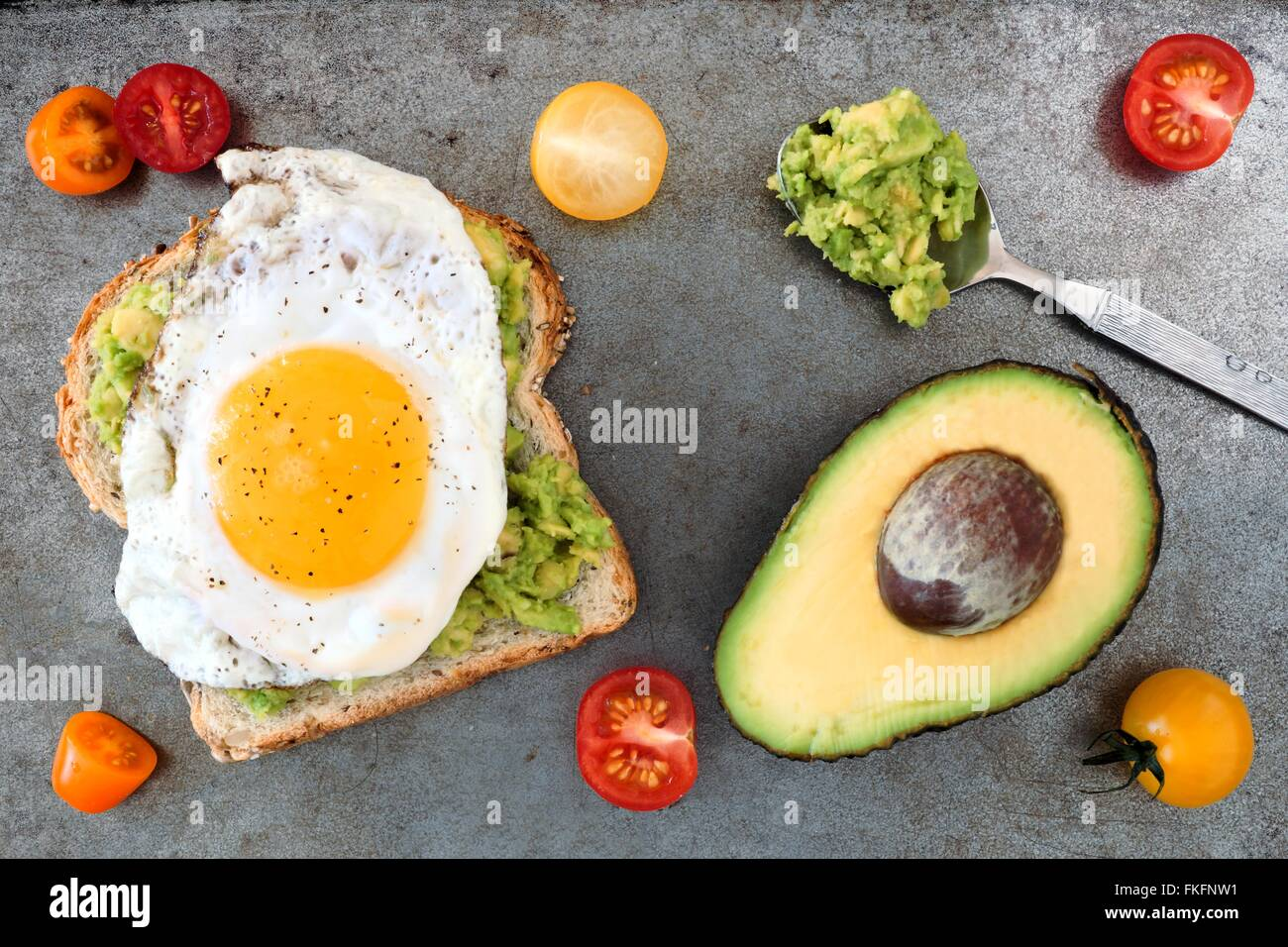 Open avocado, egg sandwich on whole grain bread with cherry tomatoes on rustic baking tray - Stock Image
