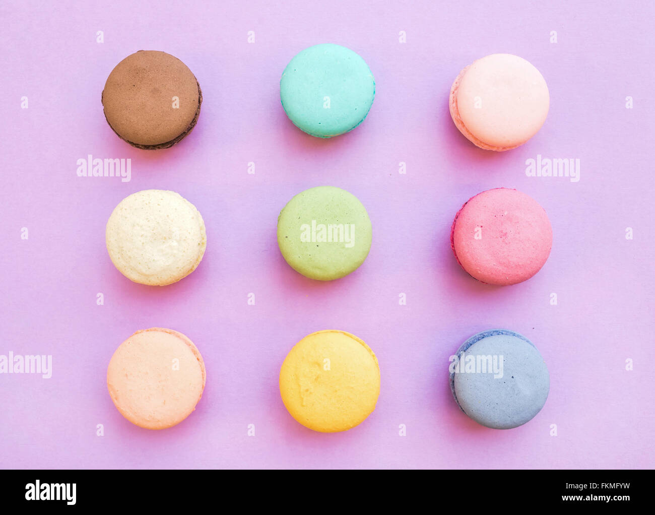 Sweet colorful French macaron biscuits on pastel pink background, top view - Stock Image