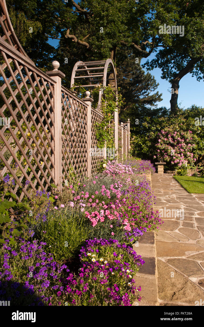 Stone paving, colourful border plants, trellis arch and screen Stock ...