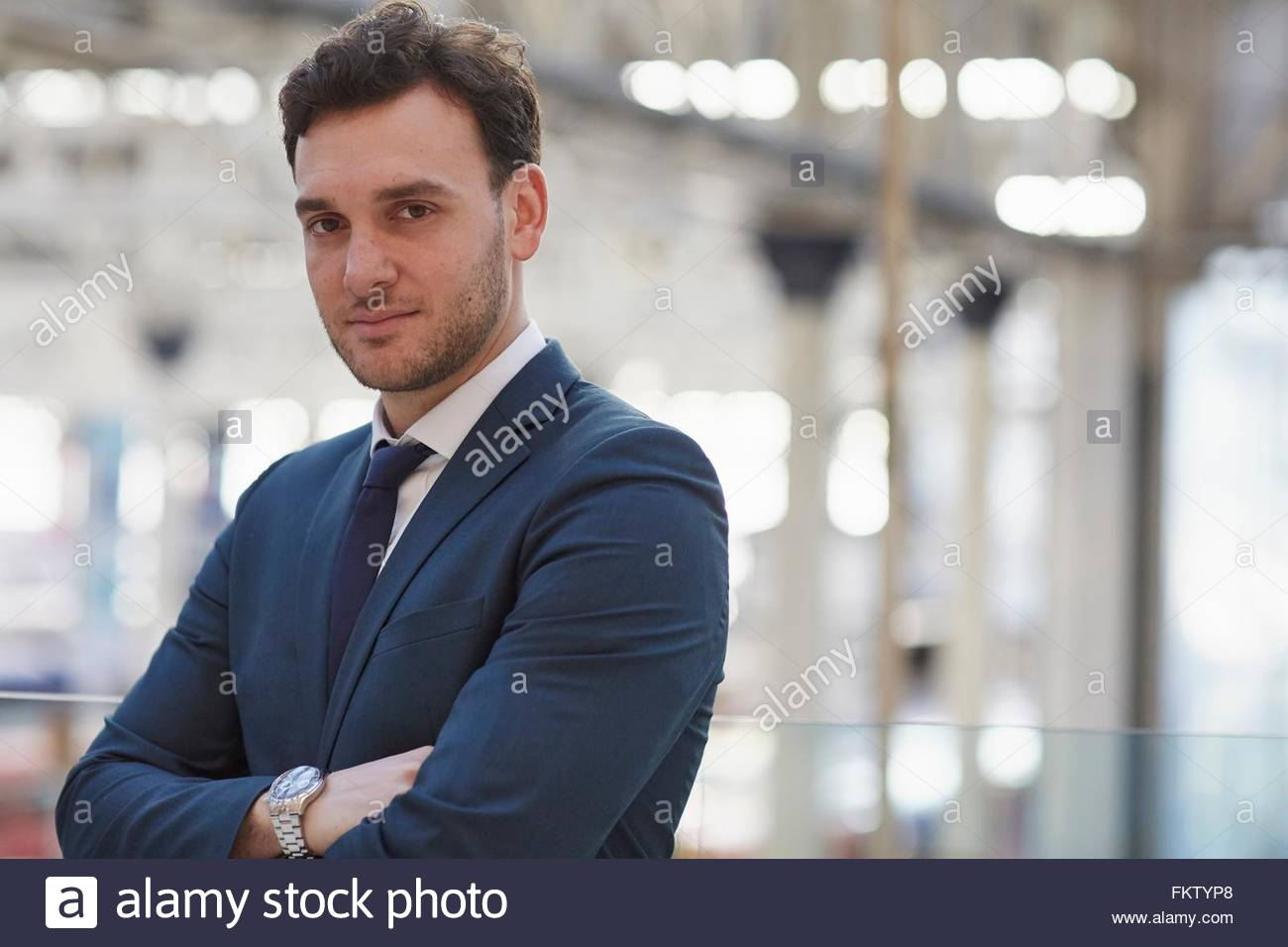 Businessman wearing suit, arms folded looking at camera smiling - Stock Image