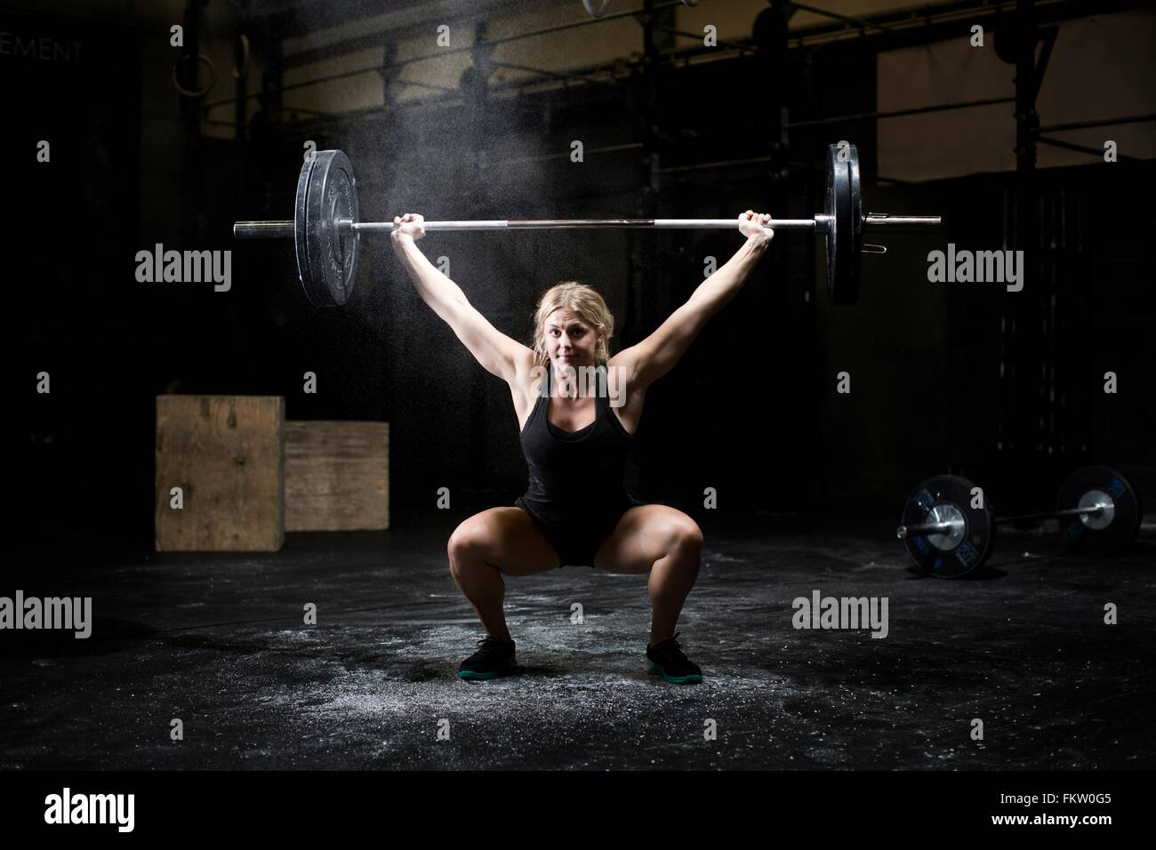 Young woman weightlifting barbell in dark gym - Stock Image