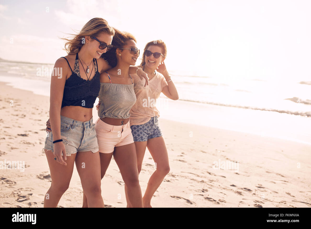 Portrait of three young female friends walking on the sea shore. Multiracial young women strolling along a beach - Stock Image
